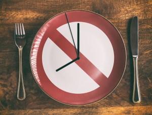 assiette vide représentant un panneau interdiction et une horloge indiquant l'heure de fin du jeûne intermittent pour pouvoir aller manger sainement