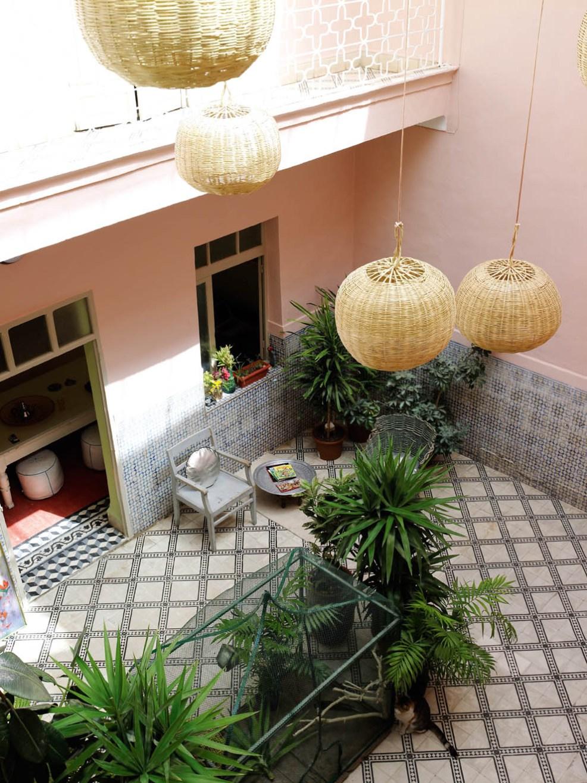 Inspiration déco avec ces photos d'une terrasse marocaine sublime, avec un petit salon d'intérieur et des grosses lampes en osier suspendues. Découvrez plus de photos dans l'article !