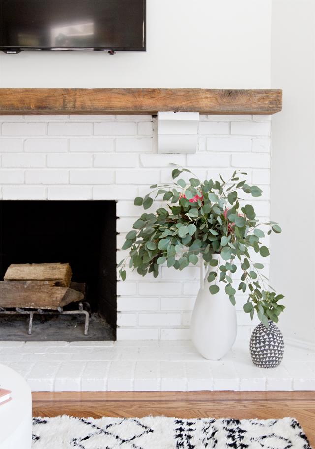 Idée déco pour décorer sa cheminée avec un vase et un bouquet d'eucalyptus