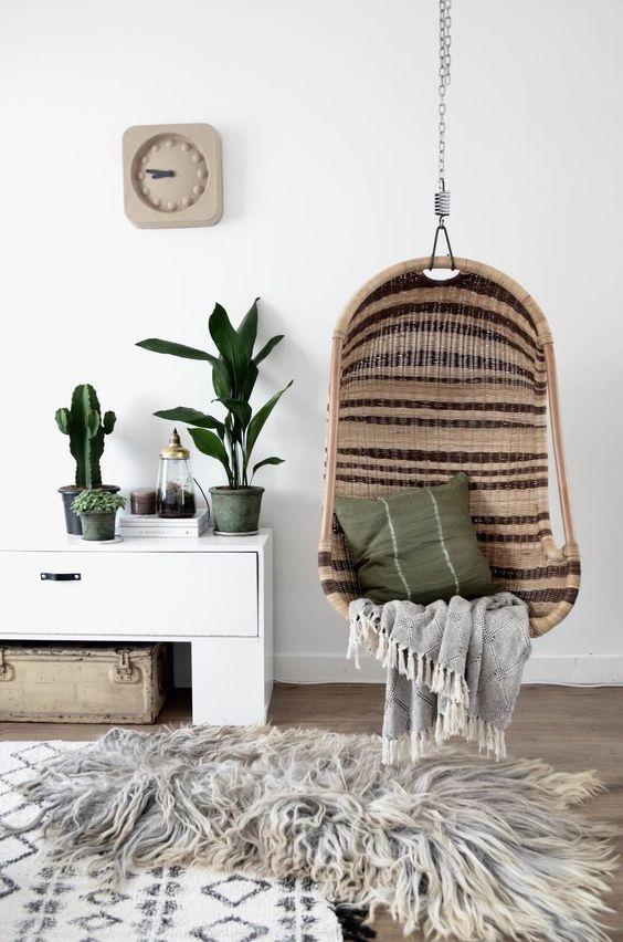 Une décoration bohème avec un fauteuil suspendu et une fausse fourrure