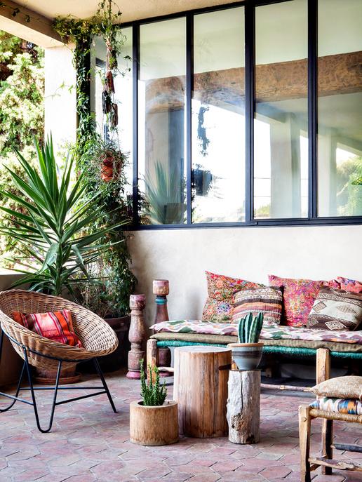 Une déco bohème d'extérieur, avec des fauteuils et bancs sur la terrasse