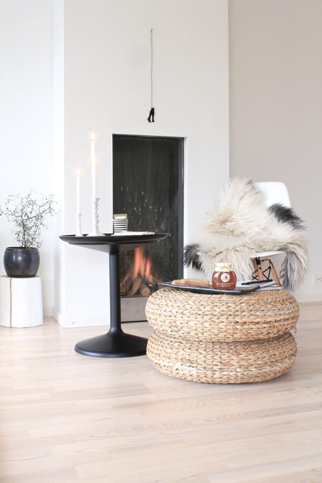 Un coin cocooning autour d'une cheminée avec bougies et rangements en jonc