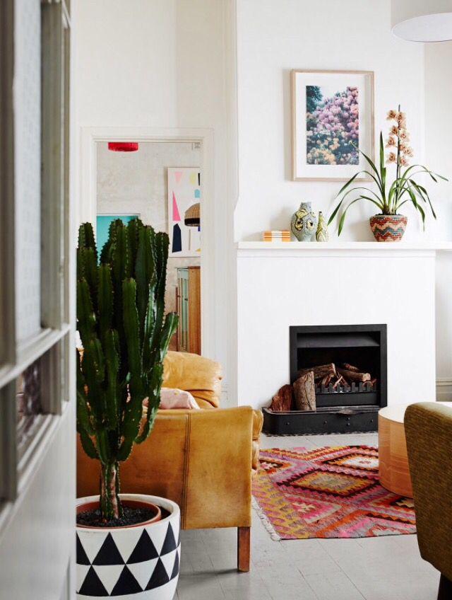 Un salon cosy avec une décoration ethnique et colorée près de la cheminée