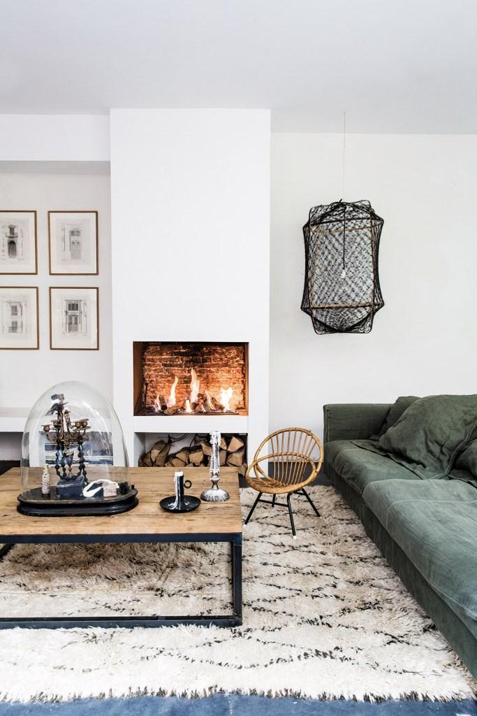 Un salon scandinave et cosy avec un tapis berbère et un sofa en velours