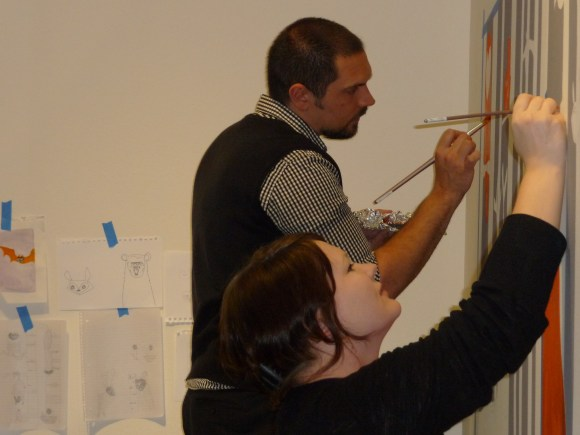 Stevie and Dan work on the mural