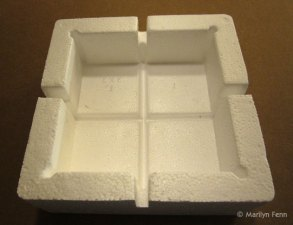 You can buy a set of 4 styrofoam corners for a little over a dollar; then score them and snap them apart.