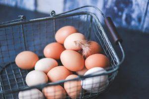 brown eggs sitting in a metal basket