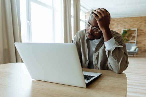 Stressed man thinking about why etsy shops close while looking at his laptop.