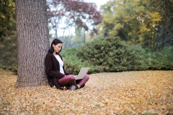 september etsy shop checklist - woman using laptop in pile of fall leaves