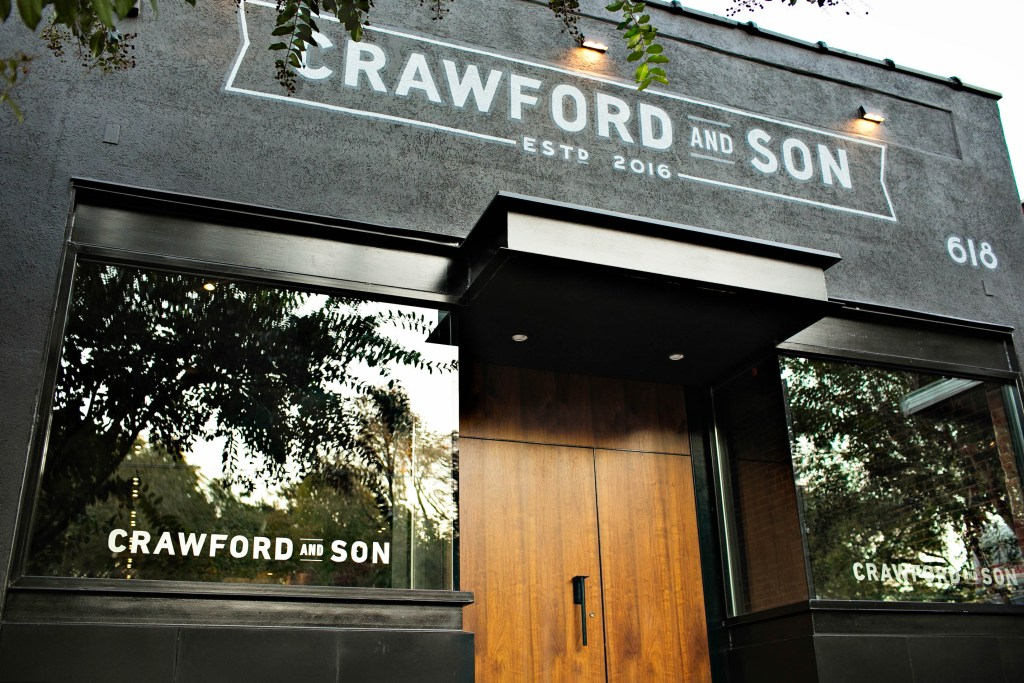 The outside of Crawford and Son restaurant is a black building with a modern, warm wood door.