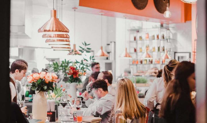 People dining under rose gold lighting amidst foliage and flowers inside Rosewater Kitchen + Bar in Raleigh, NC