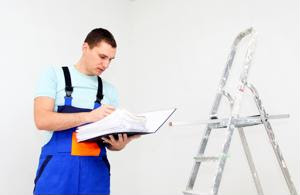 A worker inspects a ladder according to a rulebook.