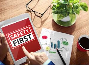 """An employee examines a tablet saying """"safety first."""""""