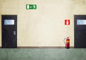 A hall with an exit sign, a fire alarm and a portable extinguisher.
