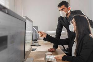 Workers wearing respiratory masks in the office.
