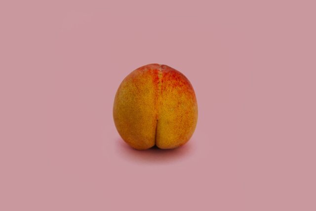Peach image on pink background about anal play