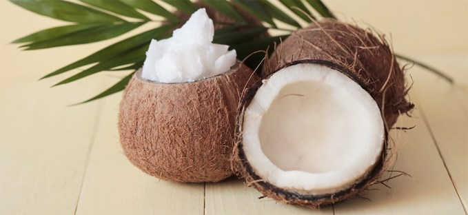 Coconuts split open on a table with coconut oil
