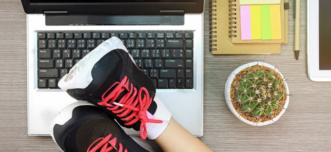 Business woman resting feet with workout shoes on desk with open laptop