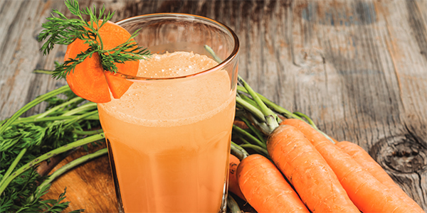 Orange Carrot Blast Smoothie on table with carrots