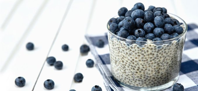 Chia Seed pudding with buleberries in a glass cup on a white wooden table with blueberries on the table