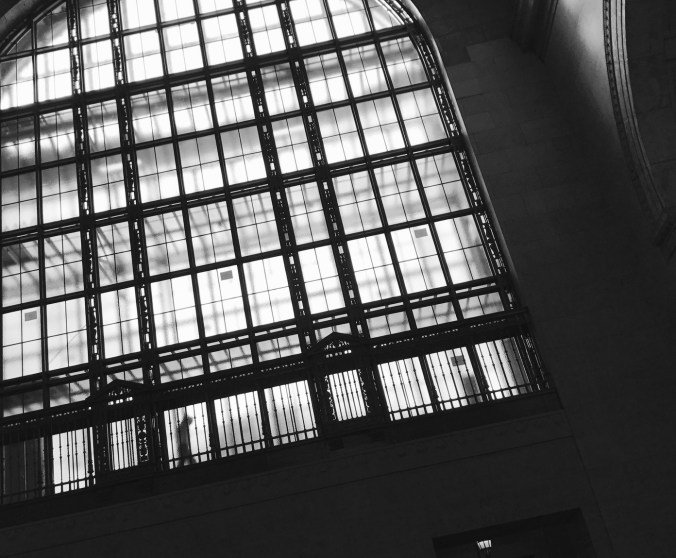 Looking up at high glass, a figure, behind it, is seen walking above Union Station. The glass is not clear, so they look like a ghost.