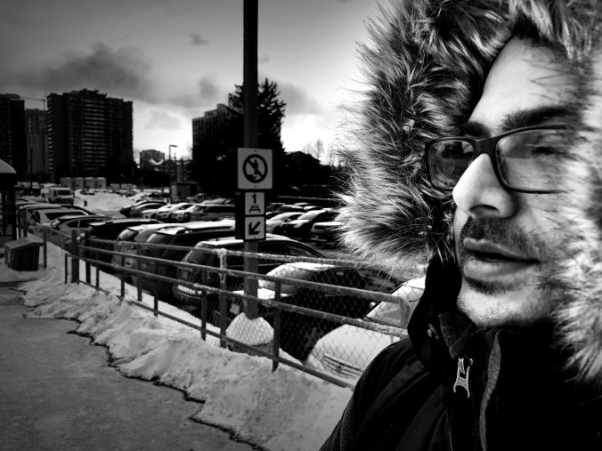 A man, bundled in a winter coat, breathes out into cold air as he waits for a GO Train.
