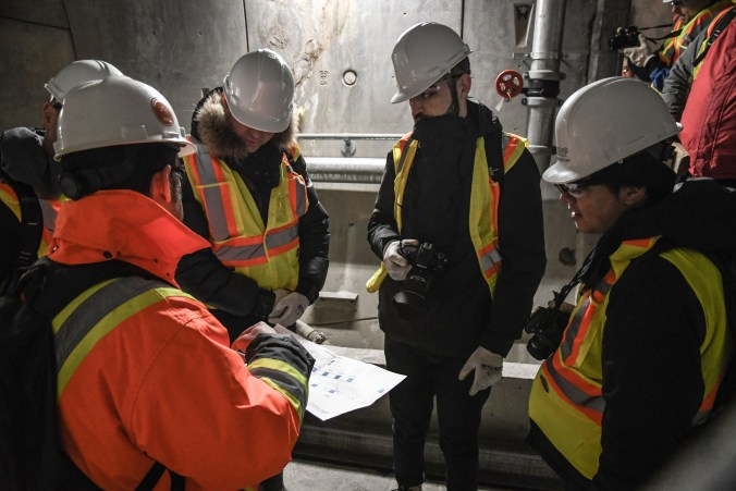 Five people, all with hardhats and vests, look down at paperwork.