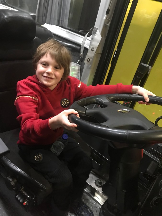A young boy, Seamus Wicksted, sits behind the wheel of the GO bus.