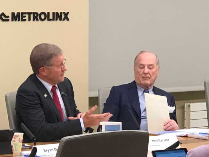 Phile Verster, Metrolinx CE, is on the left, raising his hand to make a point, as board chair Donald Wright, sits and listens to his right.