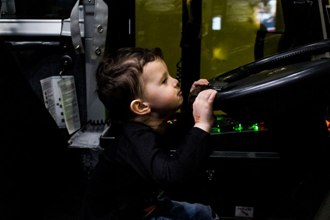 A young boy struggles to see over the wheel of the GO bus.