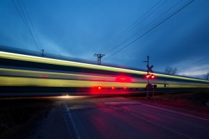 In a blurred image, a GO Transit train goes through a crossing with the warning gates down.