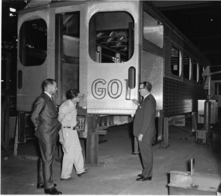 In this shot from the 1960s, three men stand looking at the GO logo being painted on the outside of a train. The image is black and white. The train is up on blocks.