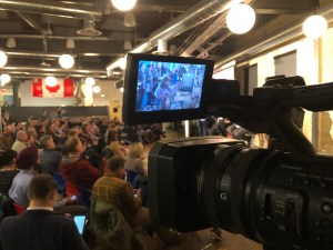 A camera points out into an audience gathered for the Ask Metrolinx event.