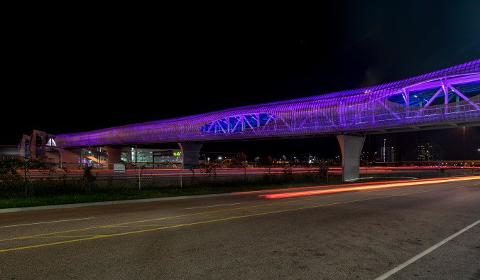 The Pickering pedestrian bridge is shown lit up in blue at night, as it stands over busy Hwy. 401.
