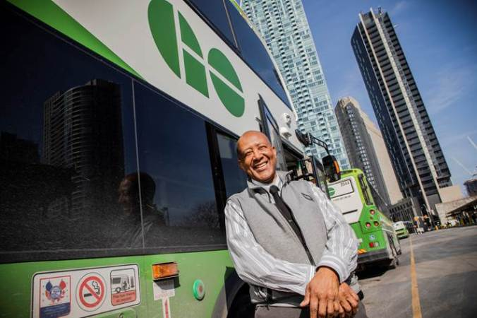 In this image from March 2019, Derrick Sealy stands outside his bus on a sunny day, smiling at the camera.