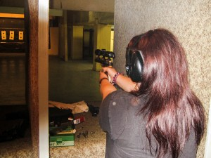 A woman, back to the camera, takes aim at targets, down range. She's standing in a shooting stall.