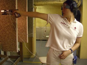 Avianna Chao is seen holding up a gun as she trains for the Olympics. Wires are hanging from the weapon.