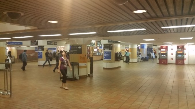 Customers walk through the halls of the old Bay Concourse. The ceiling is low and tile is brown.