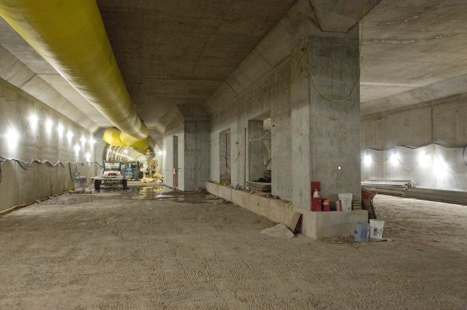 Inside the large cavern, concrete walls and equipment - along with yellow ventillation tubing - can be seen.