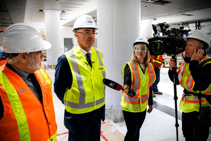 A cameraman and reporter interview two officials amid construction work.