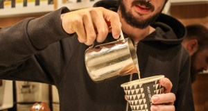 A tight shot of cream being put into a cup of coffee.