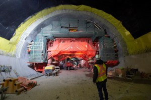 A workman looks at a tunnel, with equipment and crews working inside.