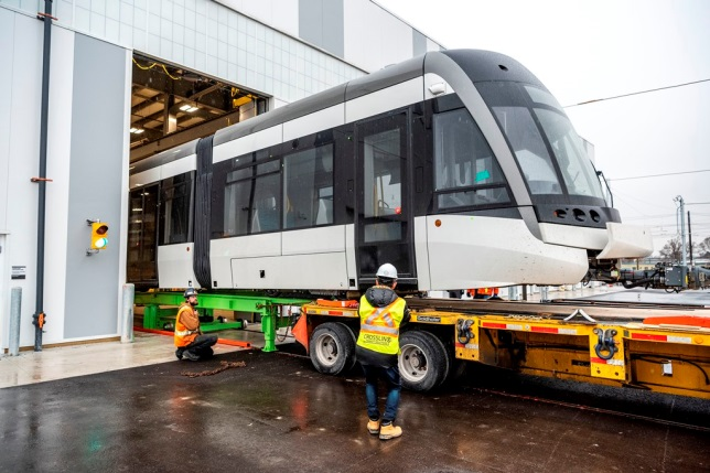 The first LRV is slowly offloaded from the flatbed of a truck by crews.