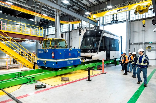 Crews inspect an arriving LRV inside a Crosstown facility. the interior is large and bright, as the vehicle is slowly wheeled in.