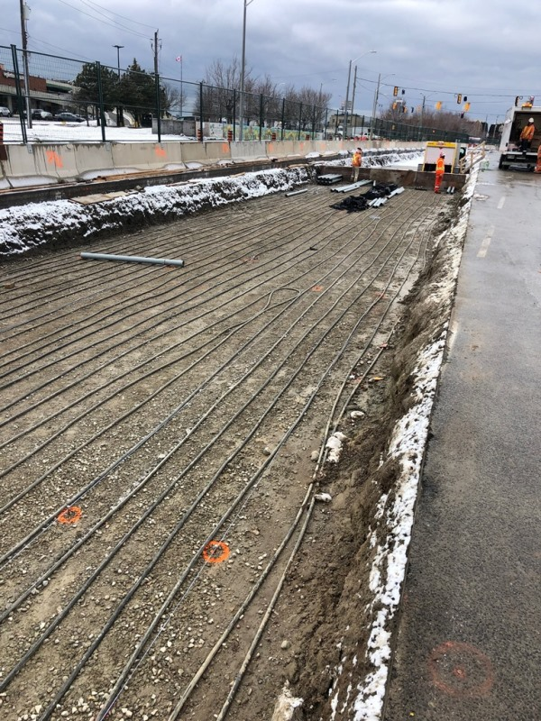 A bed of dirt and lines used before cement is put down, is shown beside a roadway.