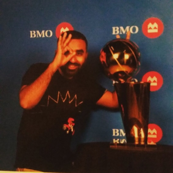 Khan beams as he poses next to the NBA championship trophy.