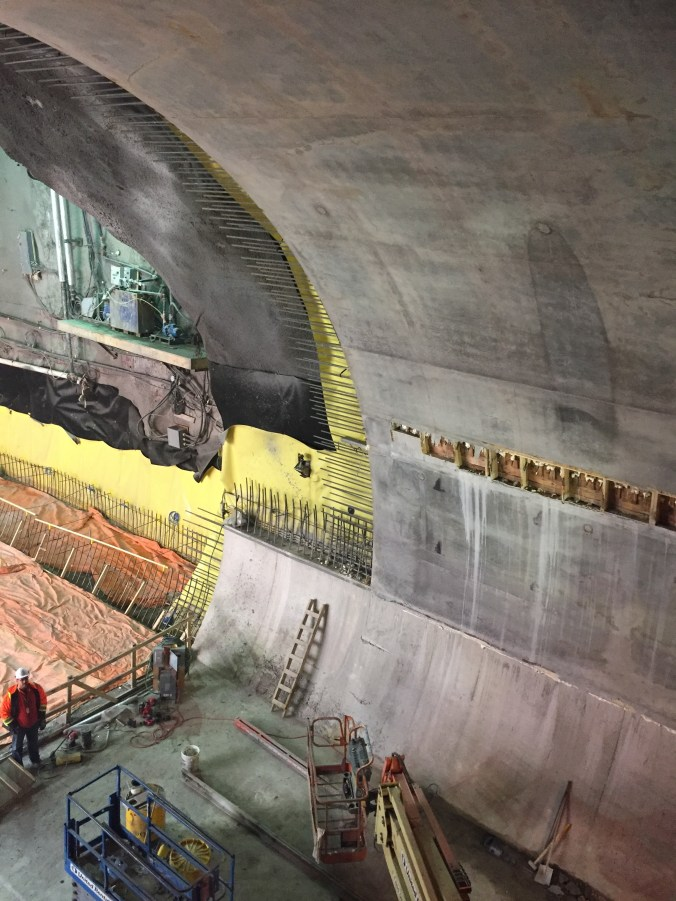 A workman looks up at a large concrete tunnel.