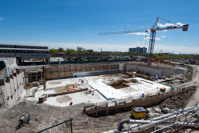 The image shows a very large, hockey-rink-like construction area, with a crane over top.