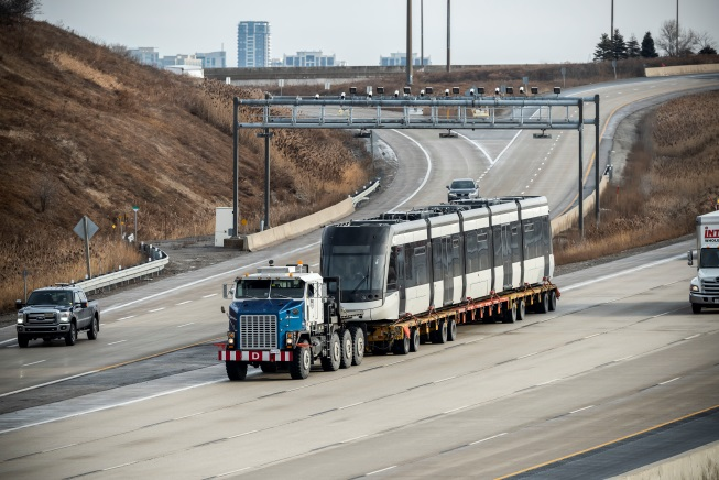 A photo shows an LRV on the back of a large flatbed truck, while driving on the highway.