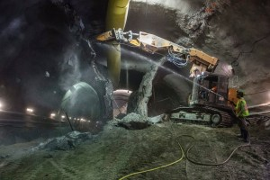 A crew member and digger chip away at rock and ground in a tunnel.